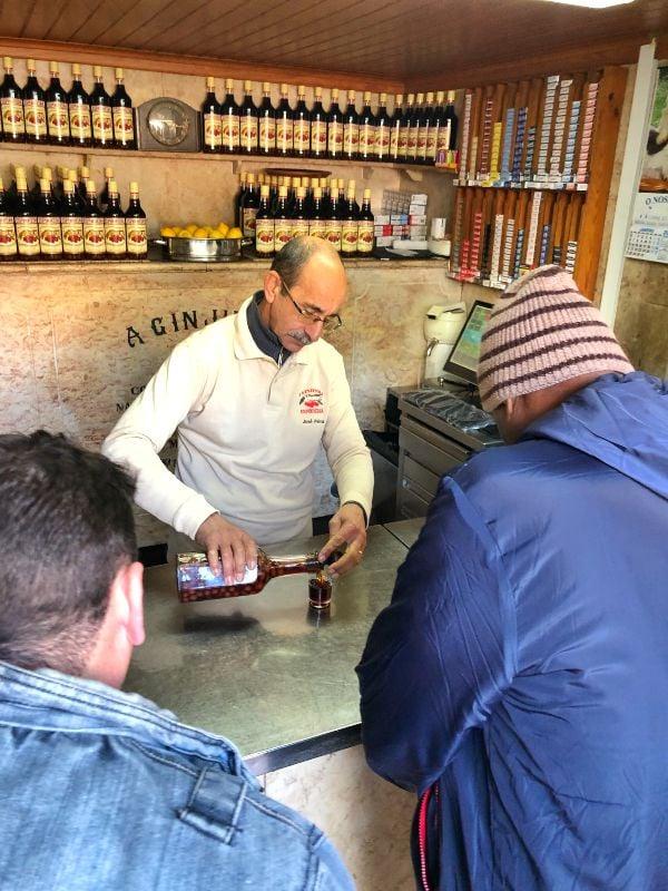 Dükkan içine bir bıyıklı amca müşterilerine ayakta vişne likörü servisi yaparken